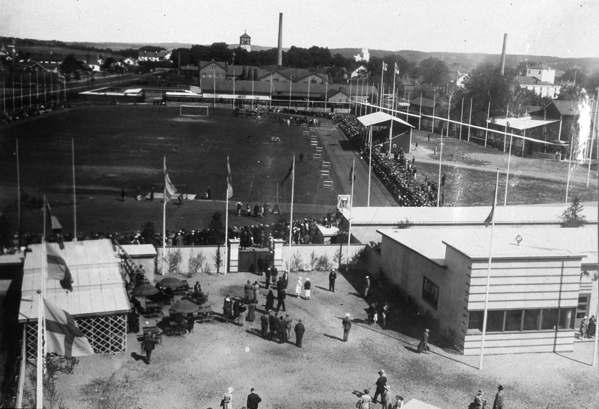 Flygfoto över utställningsområdet. En servering med trädgårdsmöbler ses till vänster. Till höger ligger en utställningshall. På Sturevallen pågår en publikdragande aktivitet. I bakgrunden, mitt i bilden, ses tornet på Sankt Nikolai kyrka och skorstenen till Arboga Margarinfabrik. Skorstenen till höger och den höga byggnaden intill, är Tekniska Fabriken Örnen, ett dotterbolag till Arboga Margarinfabrik där man tillverkade tvålen Elefanten.