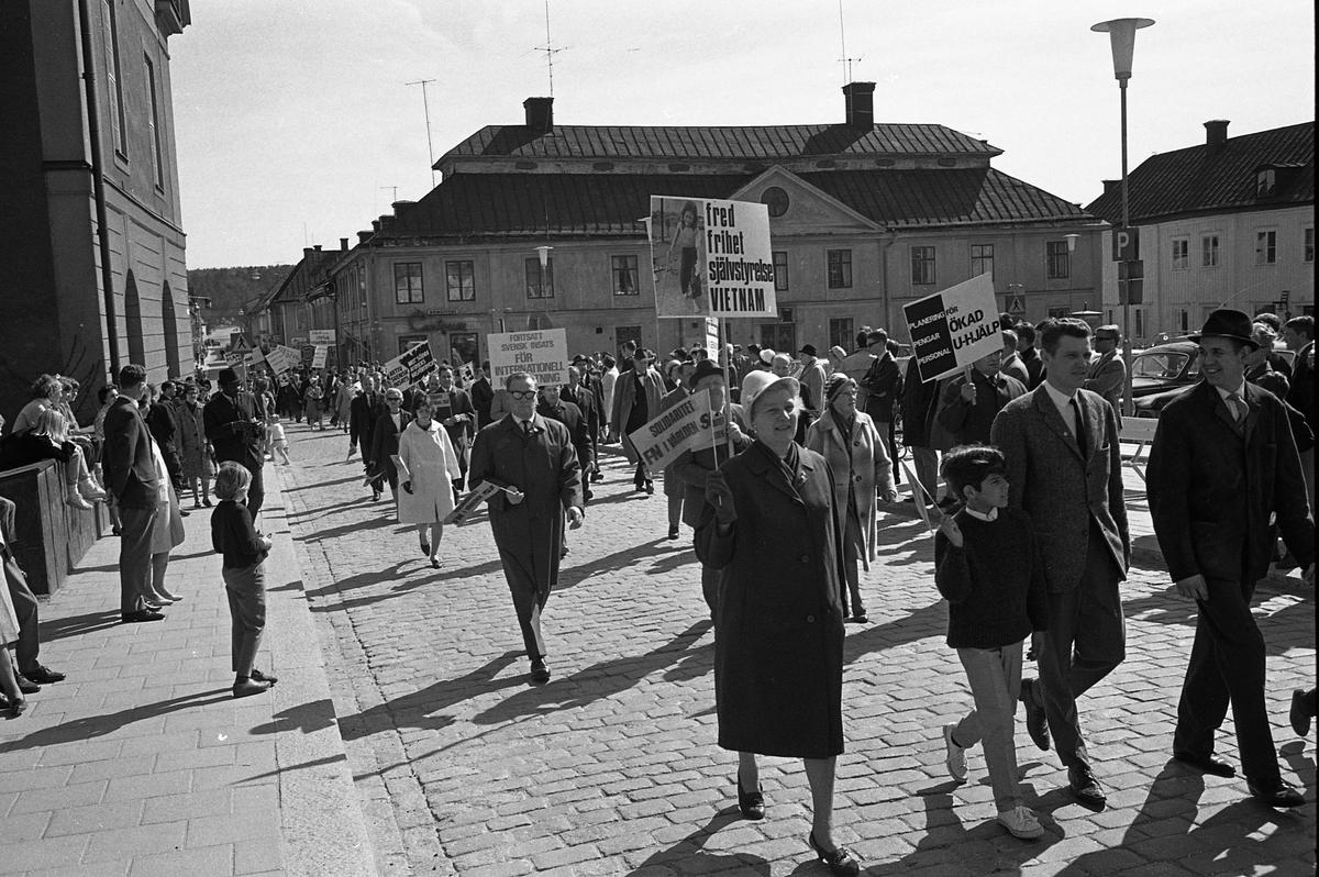 1:a majtåg. Demonstranter passerar Stora torget. Många har plakat i händerna. Människor tittar på. Till vänster ses Rådhuset, i bakgrunden ses Stadsgården och till höger ligger Stora torget.