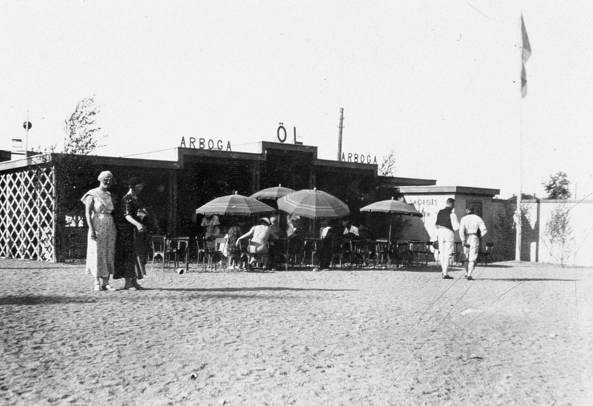 Arboga Bryggeris utställning på Arbogautställningen. Det finns en uteservering med parasoll i anslutning. Två kvinnor, i långa klänningar, till vänster i bild. Två män, i folkdräkt, till höger.