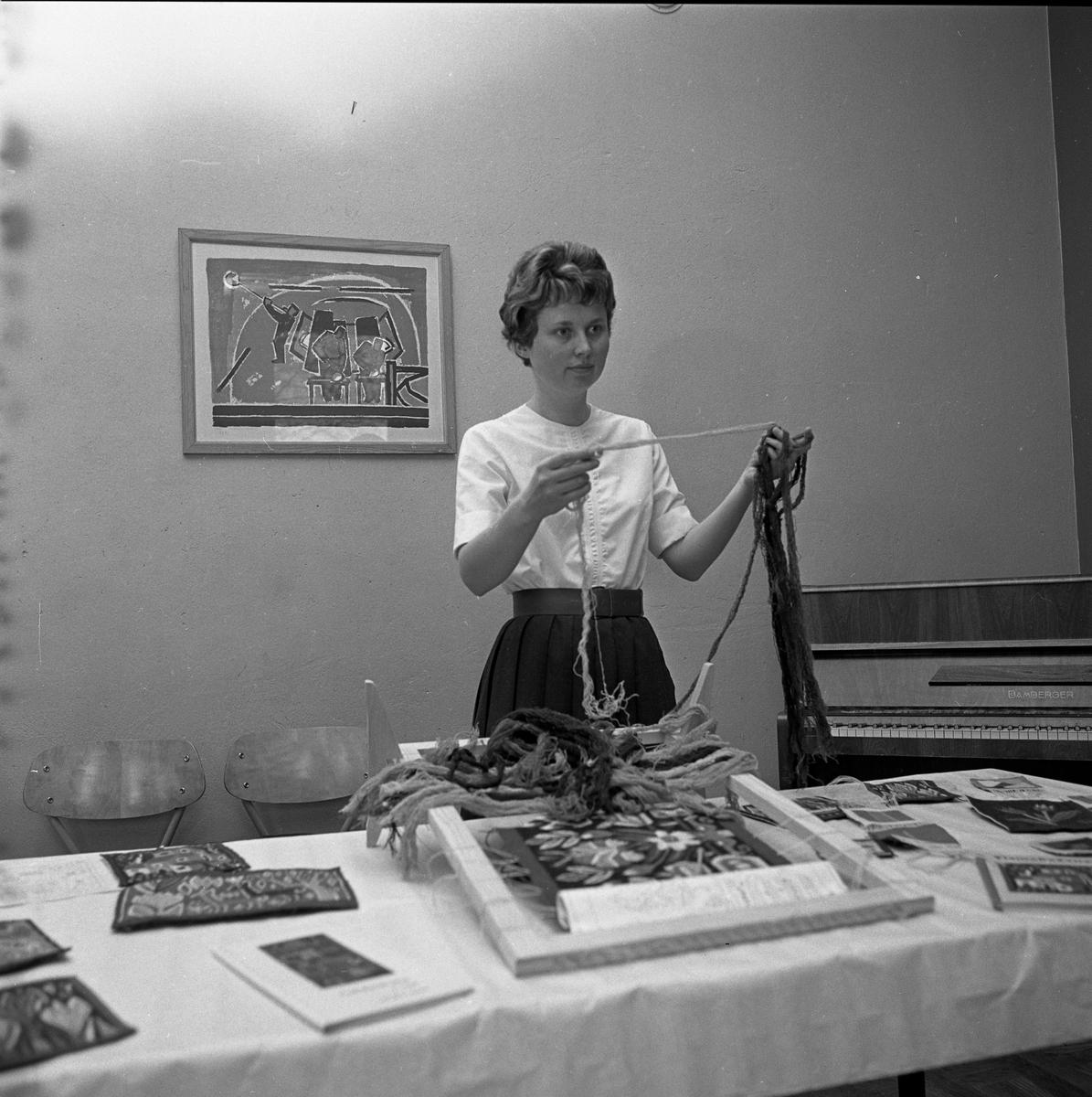 Arbetarnas Bildningsförbunds kursavslutning. En kvinna visar flamskväv i ram samt färdiga arbeten. Bilden är tagen i Fönstersalen i Medborgarhuset. I bakgrunden skymtar ett piano.