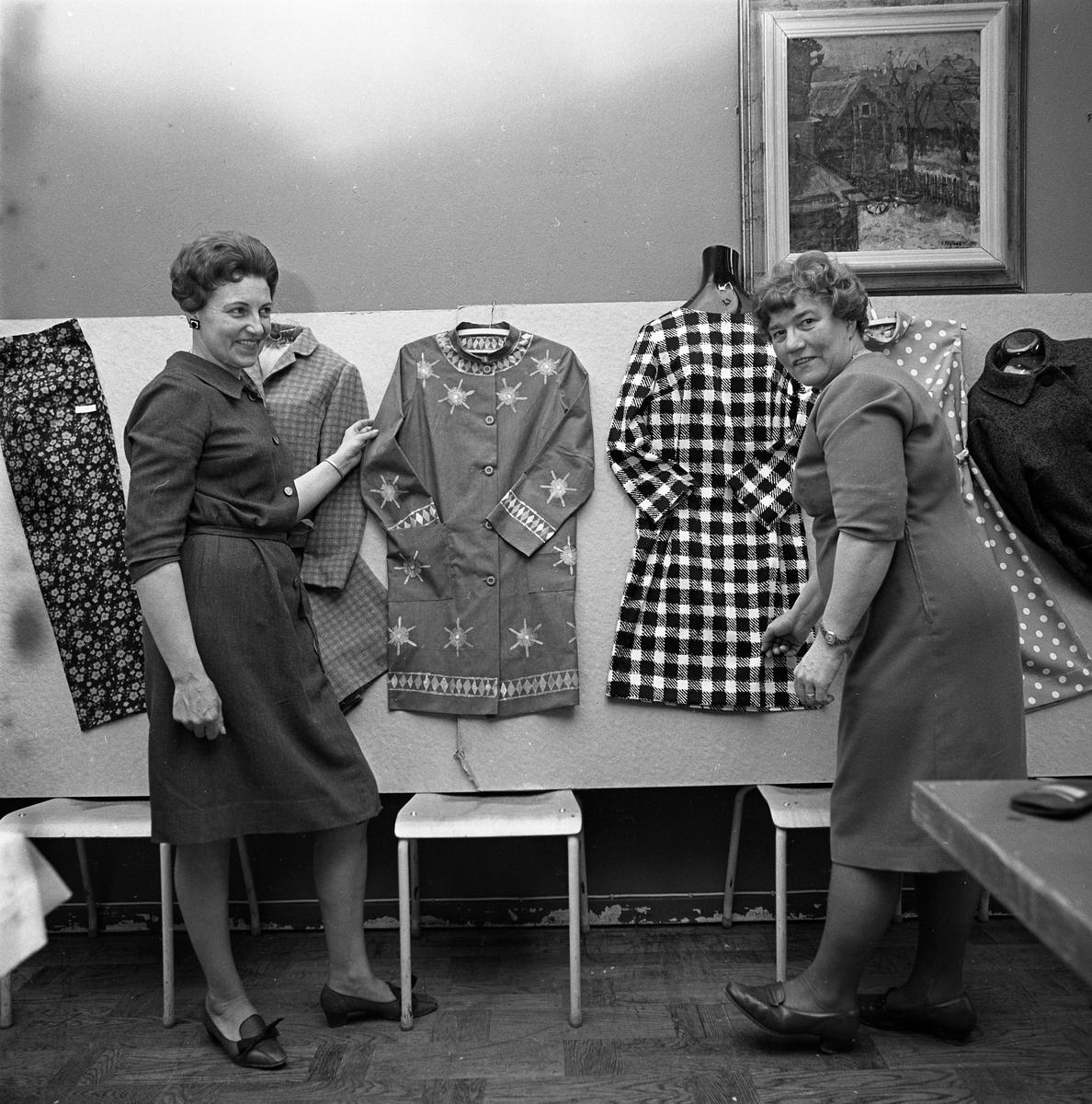 Arbetarnas Bildningsförbunds avslutning. Två kvinnor visar kläder som förmodligen sytts på kurs. Byxor, jacka, kjol, klänningar.