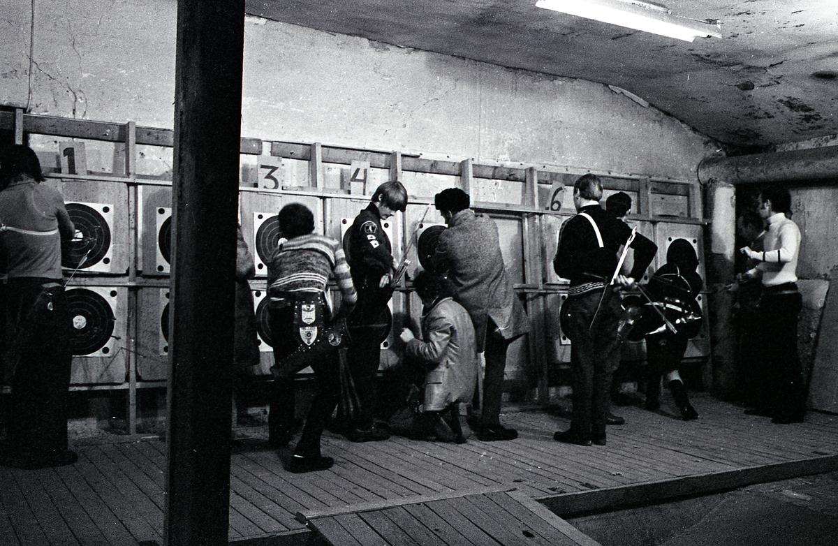 Inomhusträning hos Arboga Bågskytteklubb. Skyttarna, med sina koger hängande vid höften, räknar poäng vid måltavlorna. Lokalen ser ut att vara i en källare.