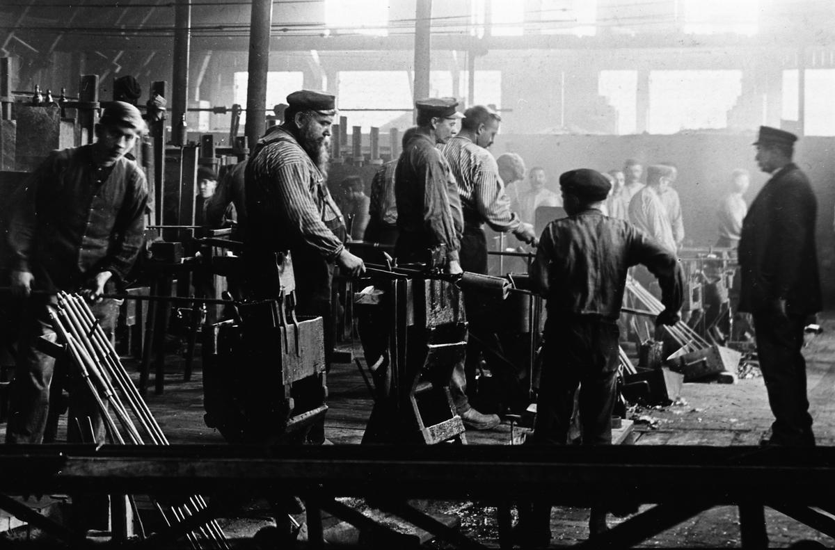 """Arboga Glasbruk, interiör. Reprofoto. En stor skara arbetare, män och unga pojkar, är sysselsatta i bruket. En del är klädda i randiga arbetsskjortor och kepsar av olika slag.  Uppgifterna om vilket år glasbruket etablerades varierar; 1867, 1870 och 1874 är exempel.  Bolagsordningen, för Arboga Glasbruks AB, stadfästes 1875. Bruket anlades nära hamnen och järnvägen. Buteljer fraktades till Stockholm med lastångaren """"Trögelin"""". På glasbruket tillverkades ca 400 olika sorters flaskor, olika storlekar inräknade. Glasbruket lades ner 1928.  Läs om Arboga Glasbruk i Hembygdsföreningen Arboga Minnes årsböcker 1982 och 2011."""