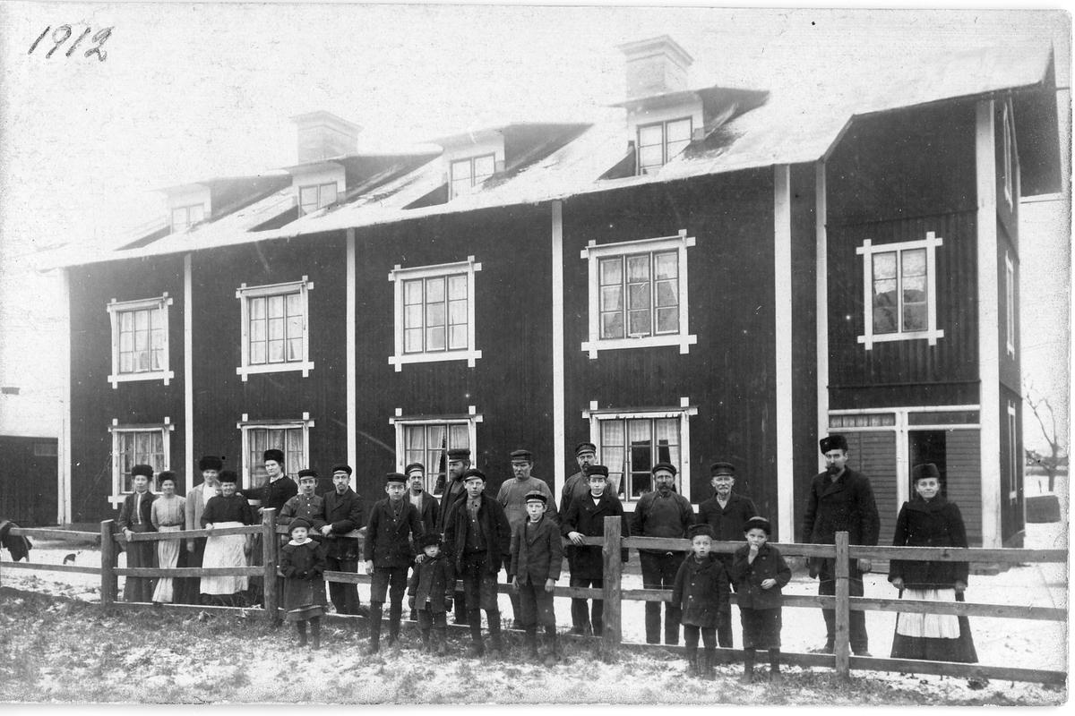 Arbetarbostad vid Arboga Mekaniska Verkstad Män, kvinnor och barn står uppradade vid staketet framför bostadshuset. Det är vinter och alla har mössor och jackor på sig. Kvinnorna bär förkläden.  Baksidan av detta fotografi, se bild 00740