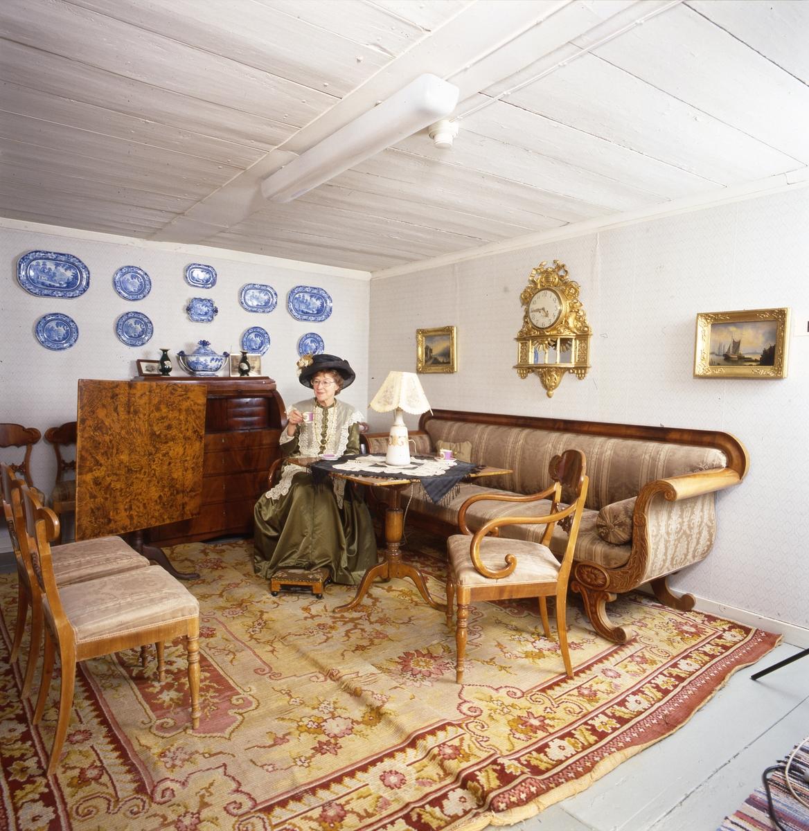 Arboga museum, interiör med Karin Lindkvist som tidstypiskt klädd kvinna.  En kvinna iklädd bredbrättad hatt, halskedja och lång, grön, spetsförsedd känning sitter vid ett bord och dricker kaffe. I rummet ses två fåtöljer, en tygklädd soffa, en fotpall, en chiffonjé och ett pelarbord med en stor lampa på. Övriga prydnadsföremål är en  soppterrin, tallrikar och tavlor på väggen. På golvet ligger en stor matta.