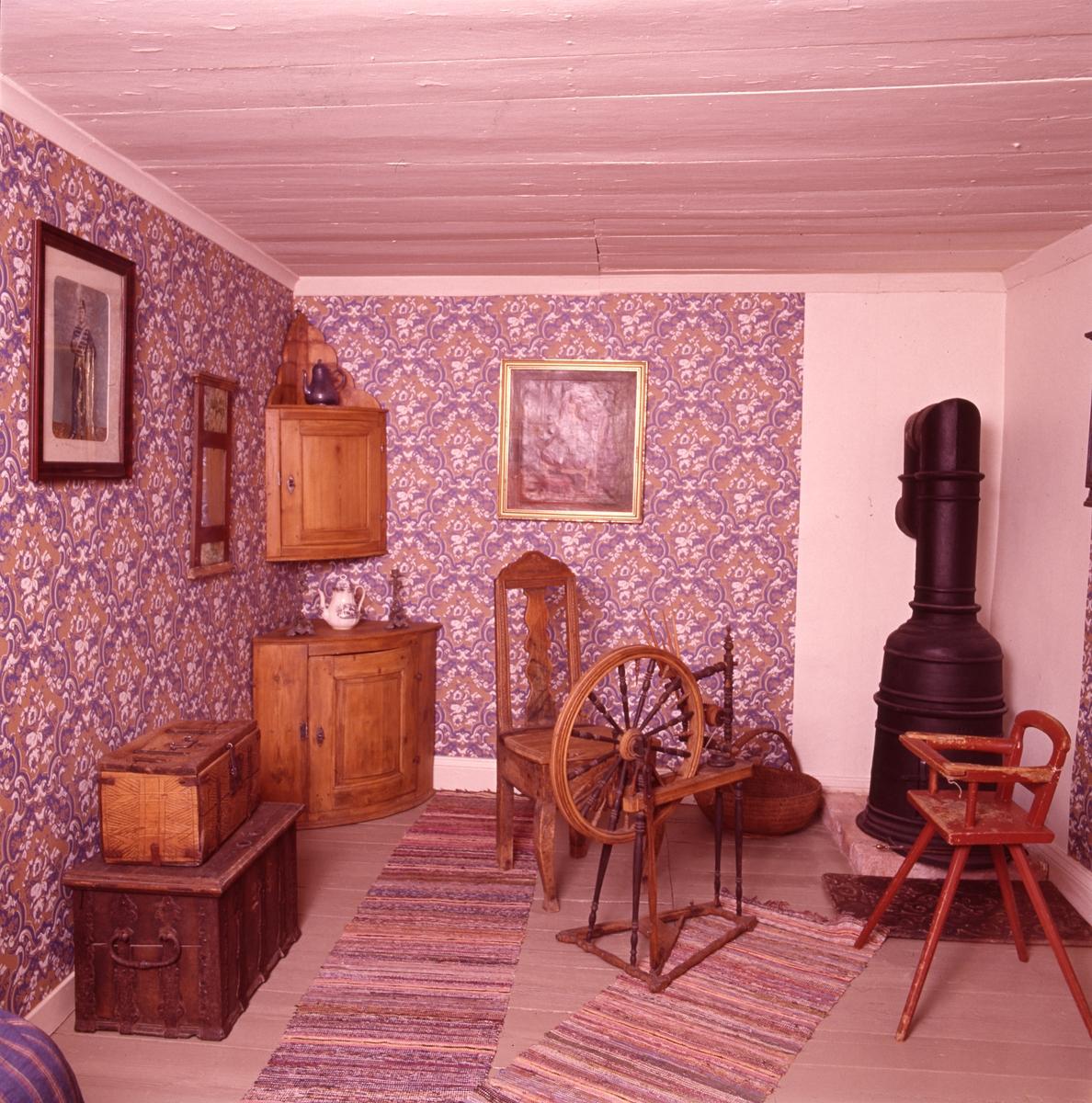 Arboga museum, interiör. En del av ett rum med stormönstrade tapeter. I ena hörnet står en kamin. Möblemanget består av ett hörngolvskåp och ett hörnväggskåp, en barnstol, två kistor i olika storlekar och en stol. En spinnrock står mitt på golvet och efter väggen står en korg. På väggen hänger två tavlor och en spegel. På golvet ligger två trasmattor.