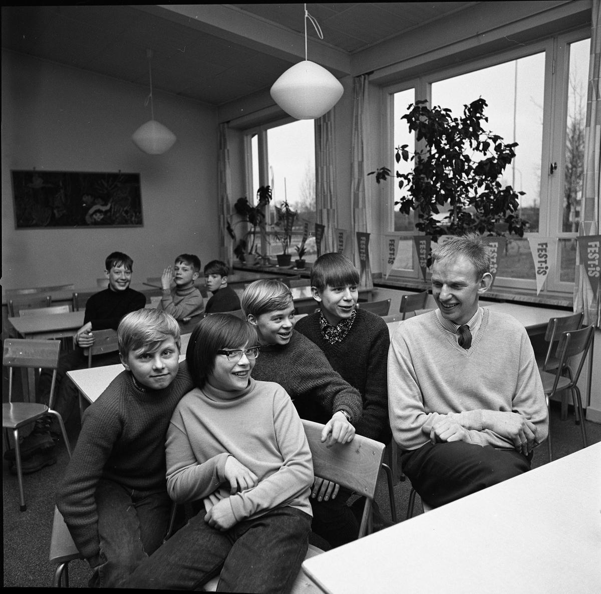 Arboga OrienteringsKlubb har ungdomsträff. En man omgiven av skolbarn. Mannen är gymnastiklärare Hans Ekberg som orienterar på sin fritid. Bilden är tagen i Gäddgårdsskolans matsal.