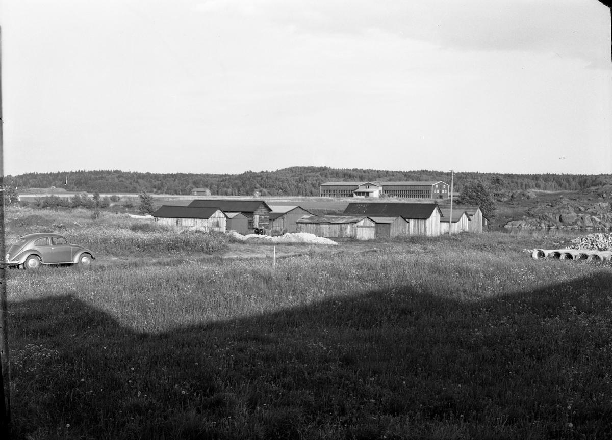 Lador på Arbogaåns norra sida. Arboga Tegelbruk syns på andra sidan ån. En folkvagn/wolksvagen till vänster. Några stora rör syns till höger i bild.  Arboga Tegelverk AB grundades 1882 och låg söder om Trädgårdsgatan och väster om Gäddgården. Företaget bytte namn till Arboga Tegelbruk 1890. Tegelbruket levererade murtegel till bland annat Arboga Bryggeri och Arboga Margarinfabrik, mycket skeppades till Stockholm. År 1938 flyttades verksamheten till området Stenlöpet. Teglet transporteras nu med lastbil. En omfattande brand, 1940, orsakade stopp i produktionen. Anläggningen byggdes upp och var snart igång igen.Tegelbruket lades ner på hösten 1970. Anläggningen eldhärjades 1971 och hela bruket lades i aska.  Läs om Arboga Tegelbruk i Hembygdsföreningens Arboga Minnes Årsbok 1999, varifrån ovanstående är hämtat.