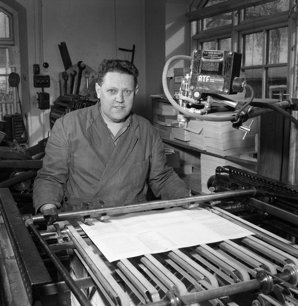 Arboga Tidning, interiör, personal. Nils Munther, iklädd arbetsrock, står vid en maskin.