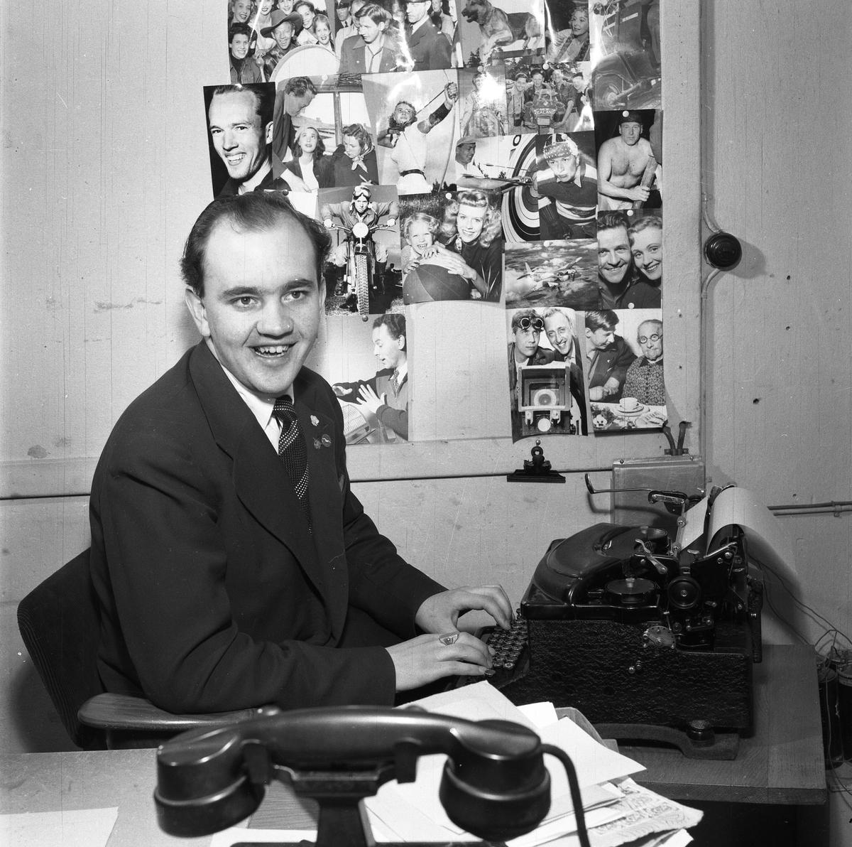 Arboga Tidning, personal och interiör. Journalisten Rune Ström vid skrivmaskinen. På väggen bredvid sitter diverse foton. I förgrunden syns en telefon.
