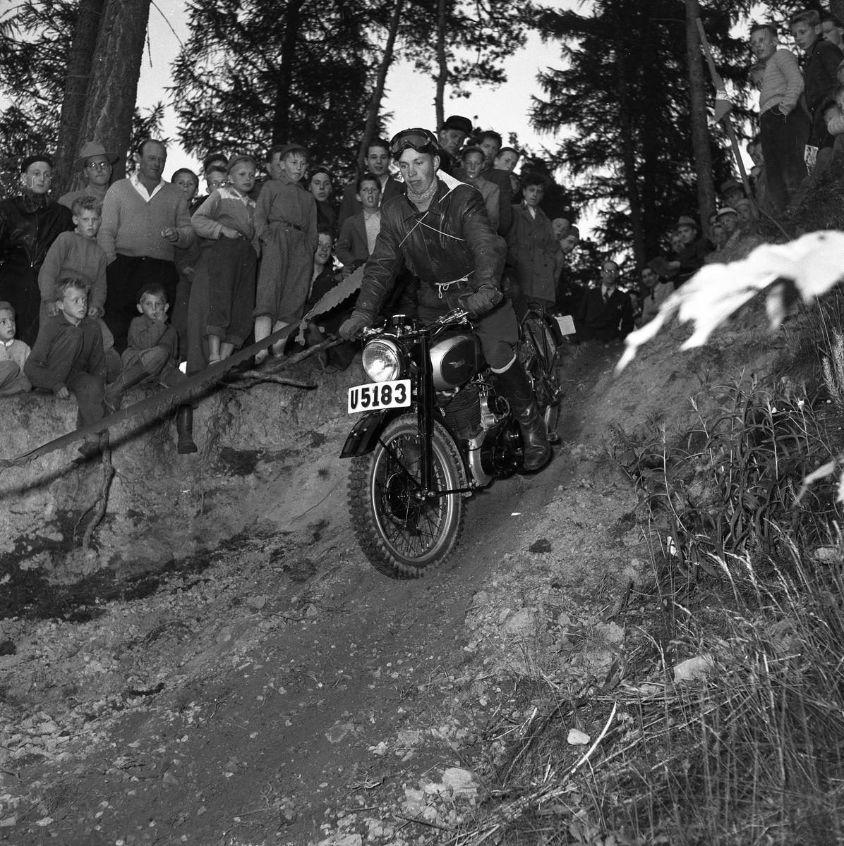 Arbogas Stjärnknutte Tävling. Man som kör motorcykel i terrräng, publiken står alldeles intill och ser på.