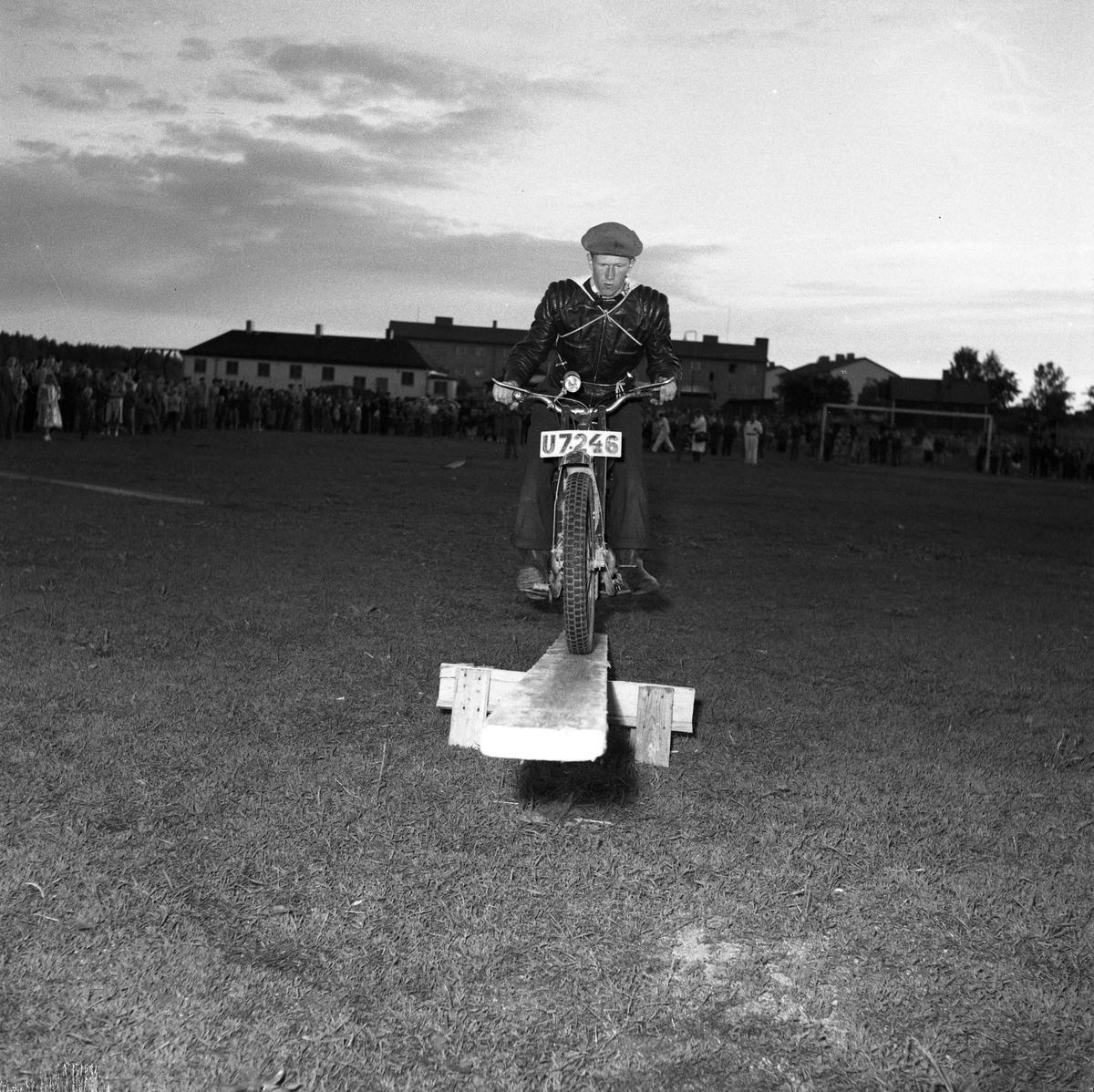 Arbogas Stjärnknutte tävling. Balansövning med motorcykel på lutande bräda Bilden ser ut att vara tagen på en fotbollsplan, på kvällen. En stor publik tittar på.
