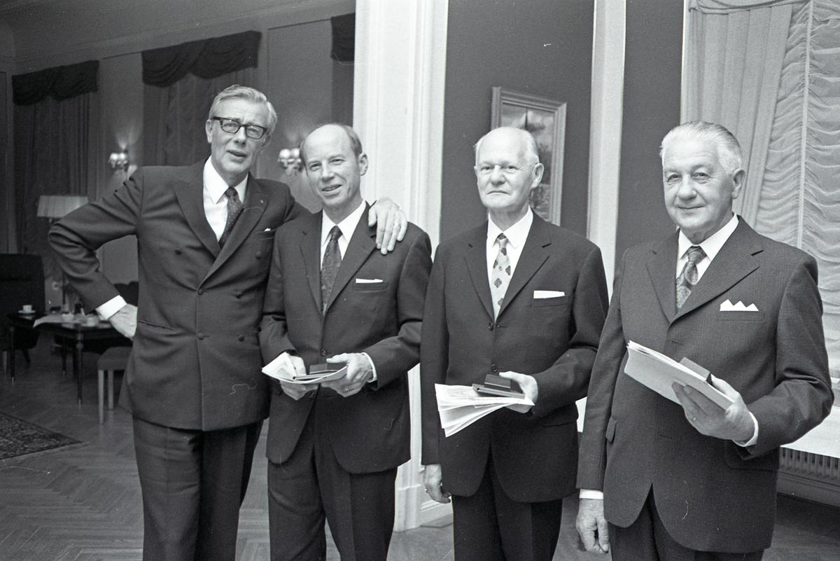 ASEA-direktör Tegström (?) med tre veteraner; Gerhard Leverfeldt, Nils Lindkvist och oidentifierad. Vid sittgruppen, i rummet intill, är det dukat för kaffe. De befinner sig förmodligen på övervåningen på Stadskällaren.