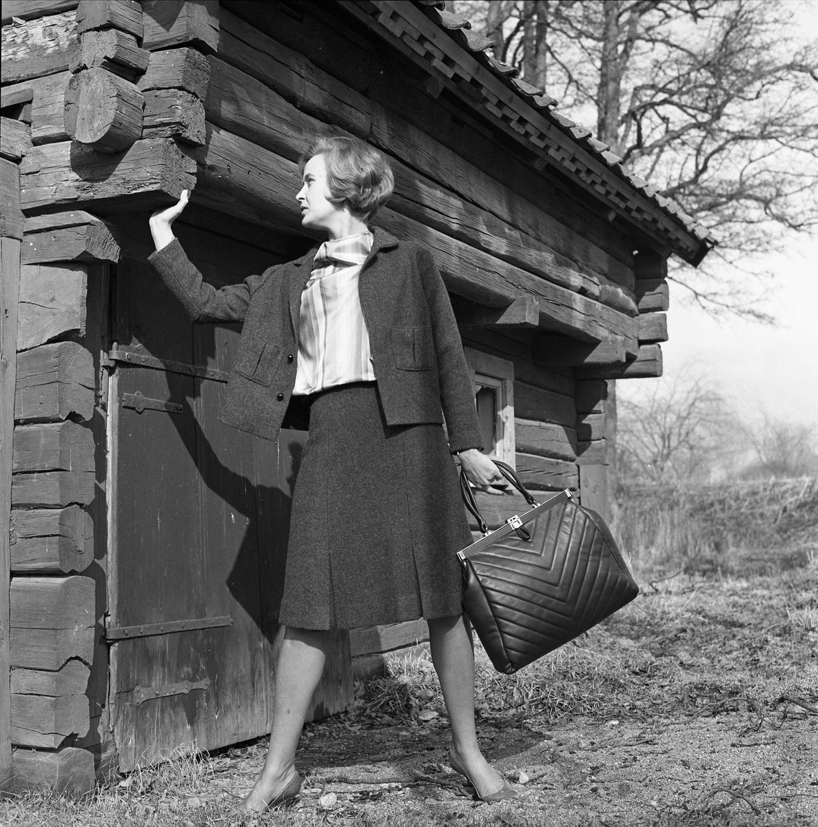 Ateljé Touché. Britt-Marie Utterström visar mode. Kvinna iklädd dräkt. Hon har en stor väska i handen. Bilden är tagen utomhus intill en äldre timmerbyggnad. Britt-Marie drev ateljén tillsammans med Marianne Rosenkvist