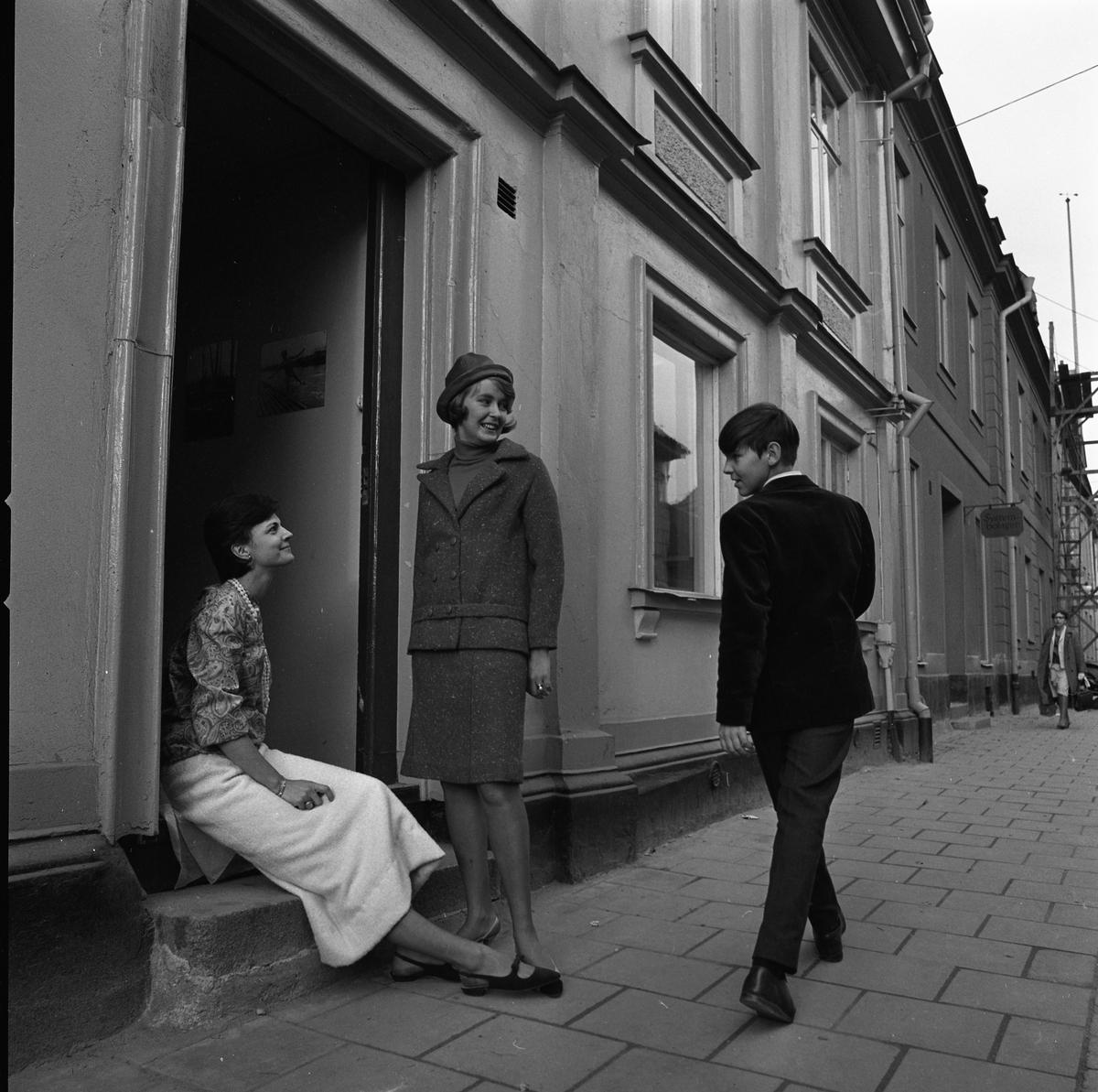 Ateljé Touché. Marianne Rosenkvist (sittande) och Britt-Marie Utterström (stående). Den unge mannen som går förbi är oidentifierad. Mode. Marianne är klädd i blus och kjol, Britt-Marie bär en dräkt och den unge mannen har en kavaj. Britt-Marie och Marianne drev ateljén tillsammans.