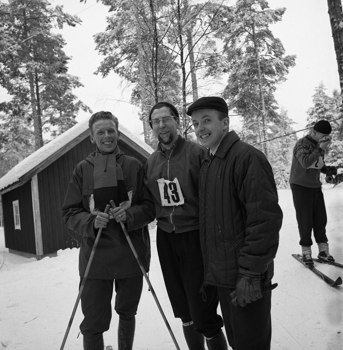 Arboga Tekniska Skola har idrottsdag med längdskidåkning. Tre män, varar två har nummerlapp på bröstet. En håller i stavar.