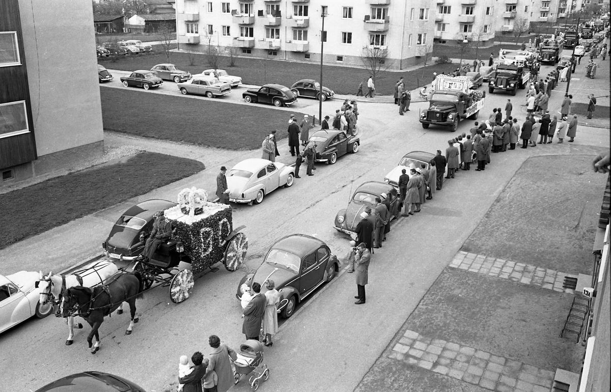 Barnens Dag firas med en lång kortege av lastbilar. Men först i bild kommer två hästar som drar en blomsterprydd vagn med bokstäverna BD. Bilar är parkerade efter gatan (som förmodligen är Österled) och publik står på trottoaren och ser på.