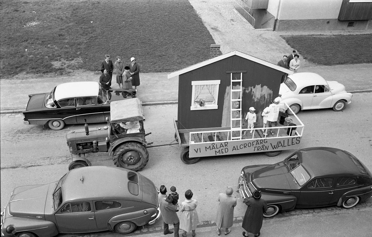 Barnens Dag firas med en parad. Här kommer en traktor med vagn. På vagnen står två personer och målar en husvägg. Där finns stege och färgburkar. De gör reklam för Walles färgaffär. Längs vägen står bilar parkerade och människor står på trottoaren och tittar på.