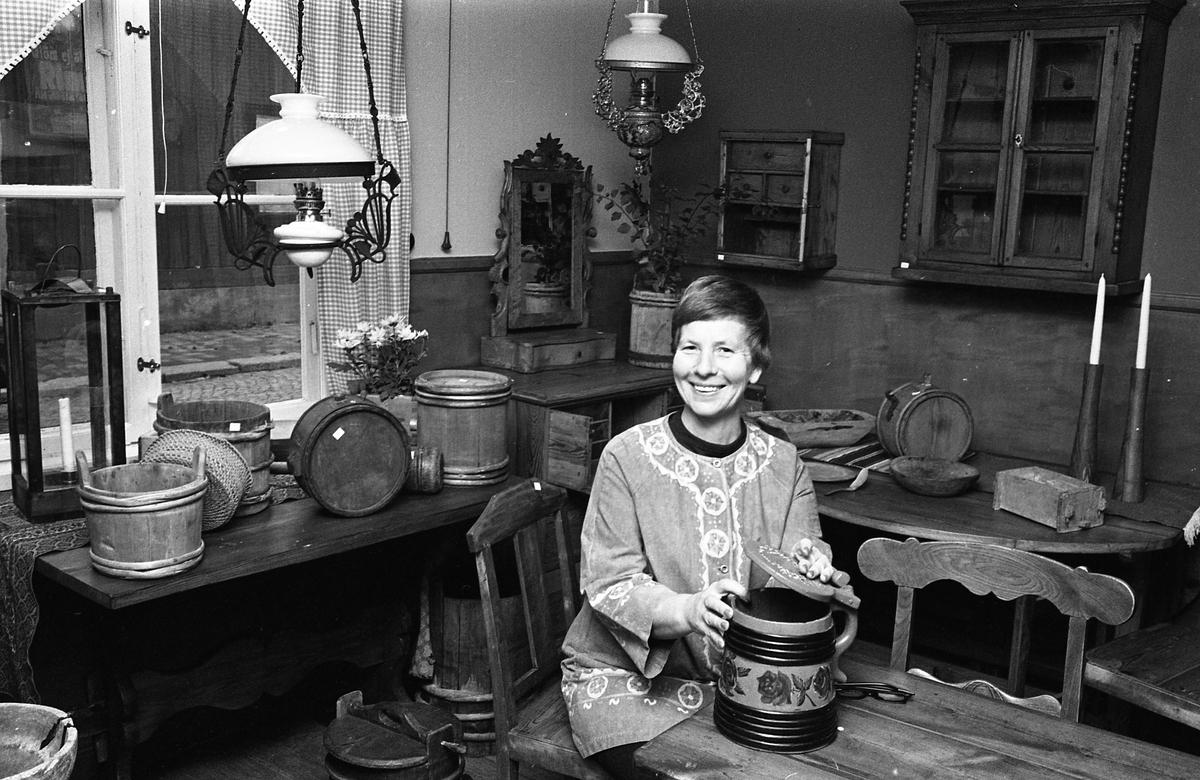 Bellas Antikbod ligger i ett blått hus på Storgatan. Kvinnan är identifierad som Blenda Asplund från Nerikes Kil. Här sitter hon och håller i en stånka. Hon är omgiven av gamla föremål som är till salu; ljuslykta, träbyttor, fotogenlampor, pigtittare, väggskåp.