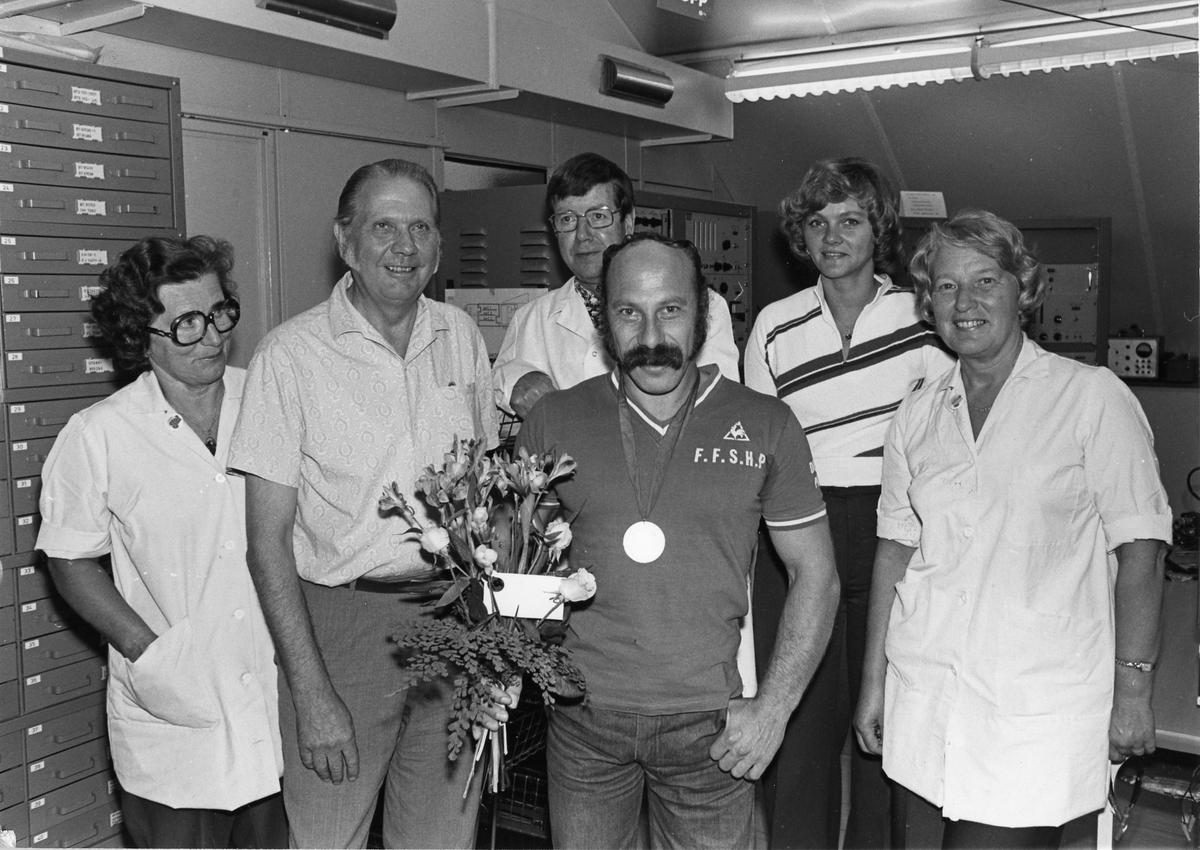 Benny Nilsson är mästare i bänkpress. Benny har en medalj om halsen och en blombukett i handen. Medaljen kan vara från Paralympics. Han är omgiven av tre kvinnor och två män. De ser ut att befinna sig på Bennys arbetsplats, i berget på CVA (Centrala Verkstaden Arboga).
