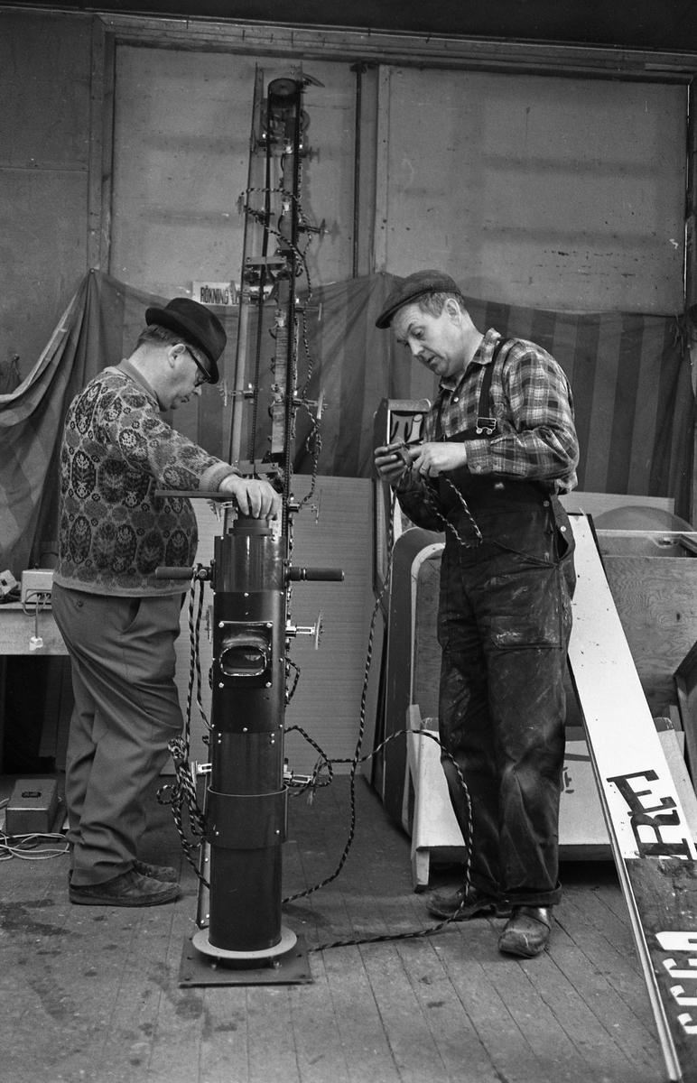 Björkmans Nöjesfält vårrustar på verkstaden vid Brunnsängsgatan. Två män studerar en mekanisk del, kanske till en karusell?