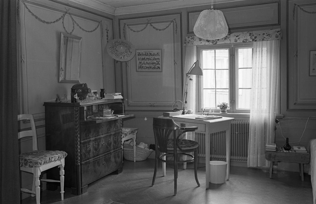 Bostadsinteriör, Crugska gården. En klaffbyrå till vänster. Framför fönstret står ett litet skrivbord med en stol till. En säng anas till höger. Tygklädd lampa i taket. Dekorerade väggar.