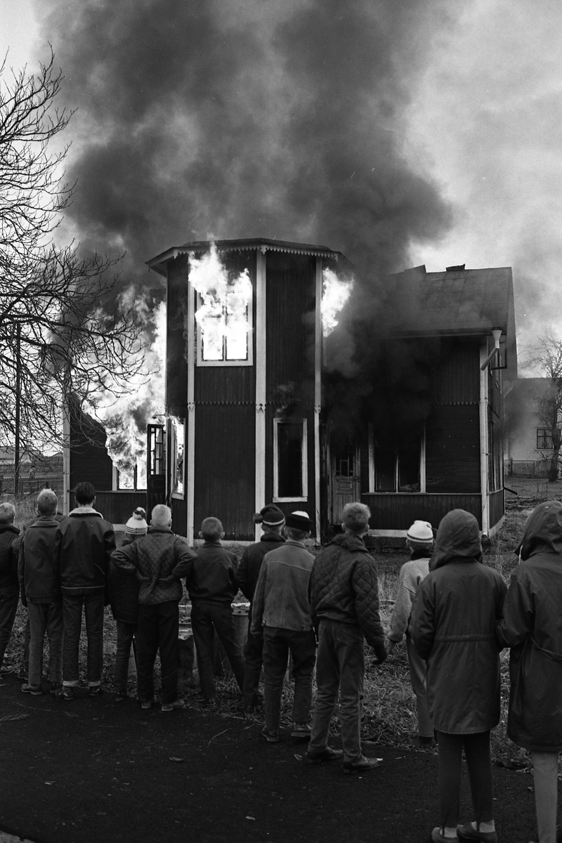 Brandövning i Sverkesta. Ett trähus brinner. Elden ses i fönstren och svart brandrök stiger mot himlen. En bit i från står människor och ser på.