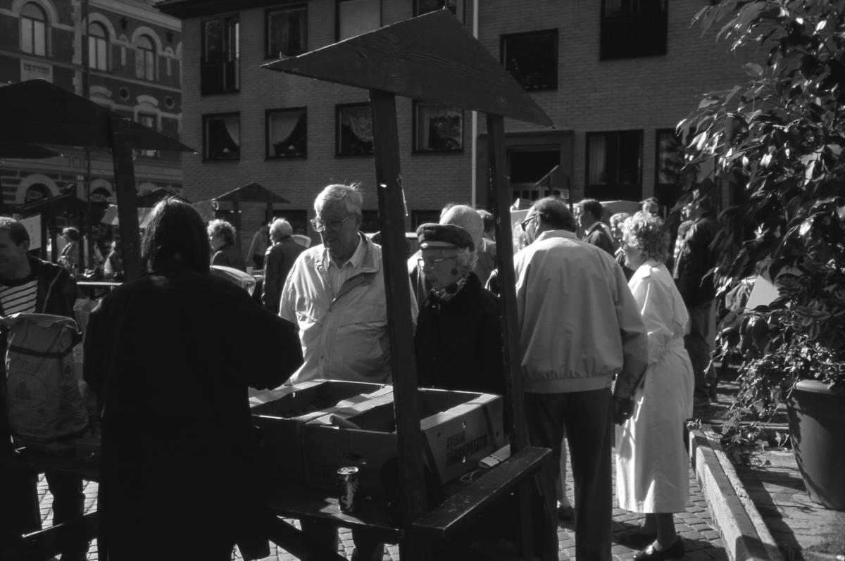 """Höstmarknaden """"Bonde på stan"""" pågår på Järntorget. Här är ett torgstånd med potatis. Ett par kunder väntar på betjäning. Till vänster skymtar """"gamla sparbankshuset""""."""