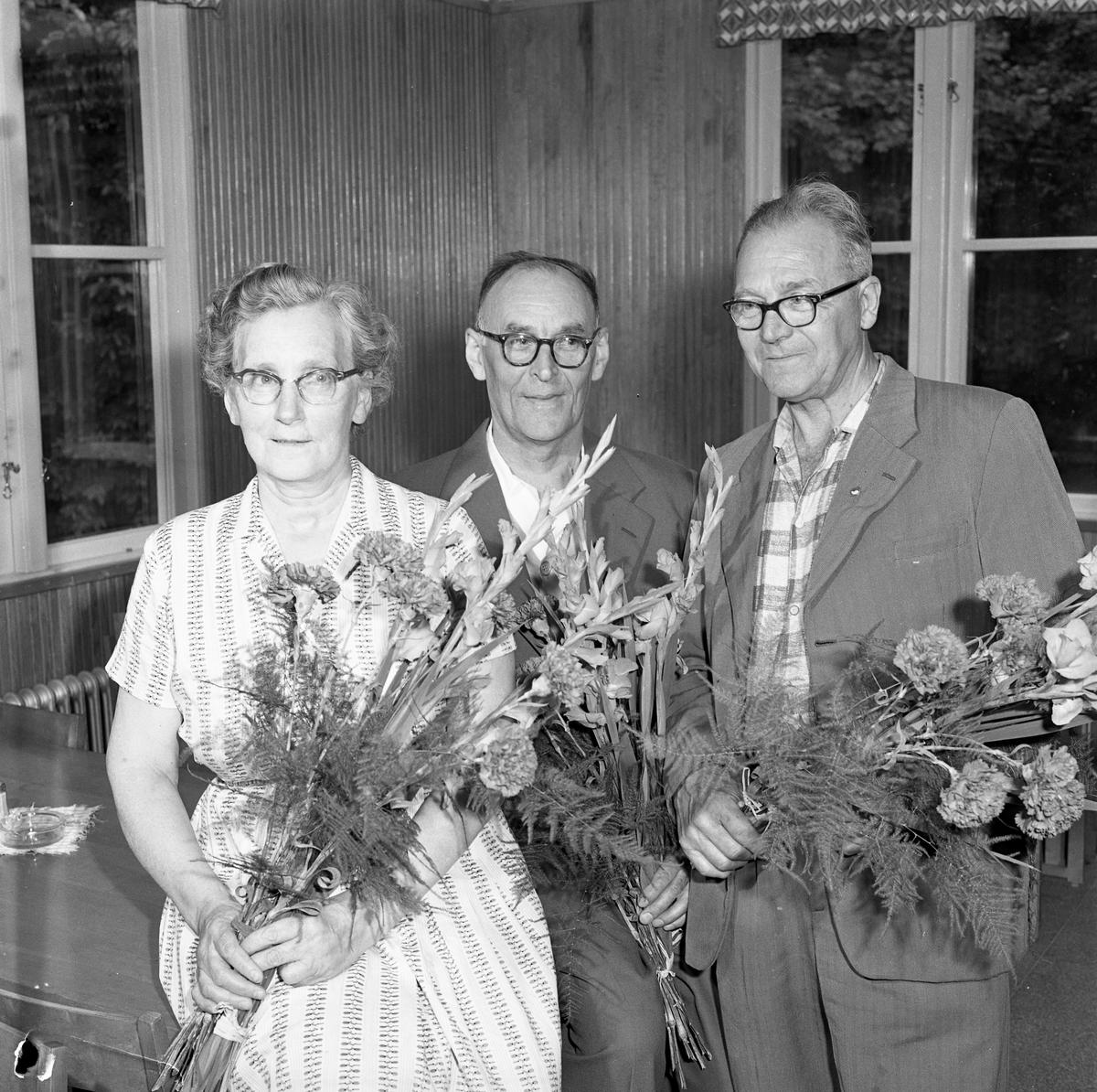 Pensionsavtackning på CVA. Mannen i mitten heter Nils Andersson. En kvinna och två män. Alla har blommor i famnen. Centrala Verkstaden Arboga