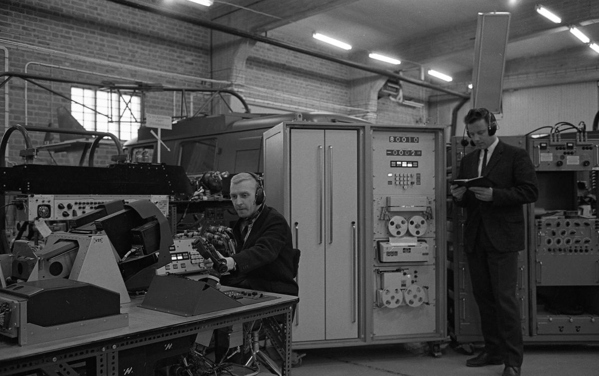 CVA interiör. Autotestare. Två män med hörlurar arbetar med stora instrument. Mannen som sitter ner heter Seth Franzén. Centrala Verkstaden Arboga