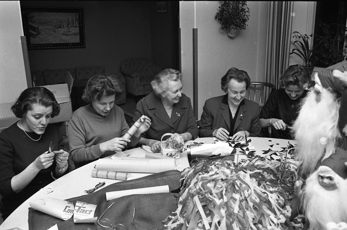 Lions damer julpysslar med silkepapper, tomma köksrullar och snören. En hög med julgranskarameller ligger på bordet. Där tronar även två skäggiga tomar. Runt bordet sitter, från vänster: Berit Munkberg, Siw Rudengård, Lilly Hedlund, Ella Högfeldt och Siri Wallström Möjligen befinner de sig på Stadskällaren
