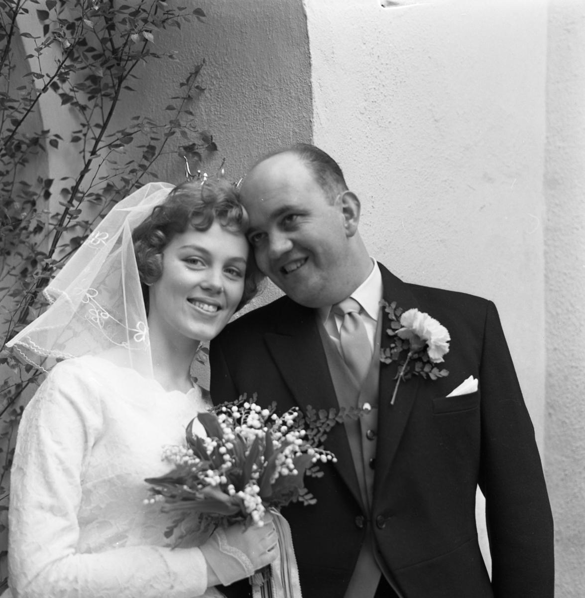 Margareta Einarsson och Rune Ström har gift sig i Heliga Trefaldighetskyrkan. Här ses brudparet vid den lövade kyrkporten. Bruden bär slöja, krona och handskar. Brudbuketten består av liljekonvaljer. Brudgummen har en nejlika på frackslaget. Porträtt.