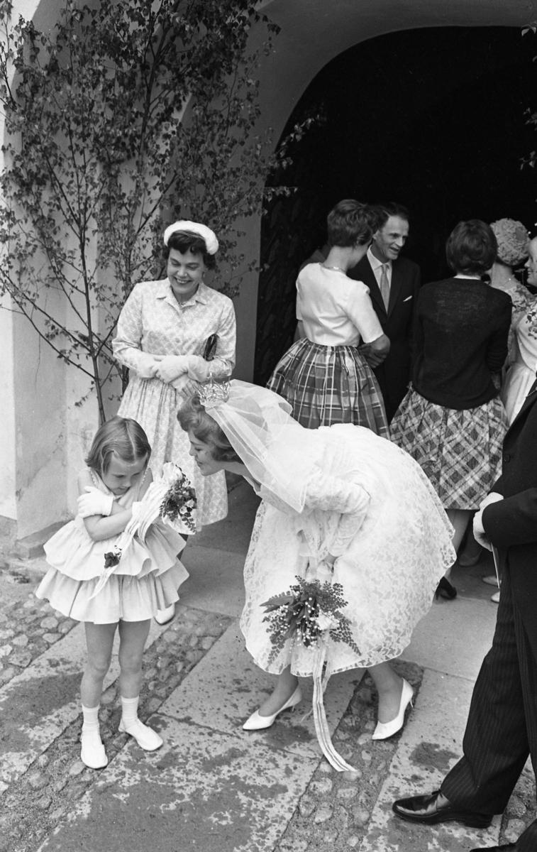 Margareta Einarsson har just gift sig med Rune Ström (han anas till höger i bild). Margareta talar med brudnäbben. Bruden bär slöja, krona och handskar. Hennes brudbukett består av liljekonvaljer. I kyrkporten står Einar Pettersson, Margaretas far. Kvinnan vid hans sida, iklädd hatt, är Ingrid Pettersson, brudens mor. Med ryggen mot fotografen, i mörk överdel, står Harriet Malmberg Svanberg.