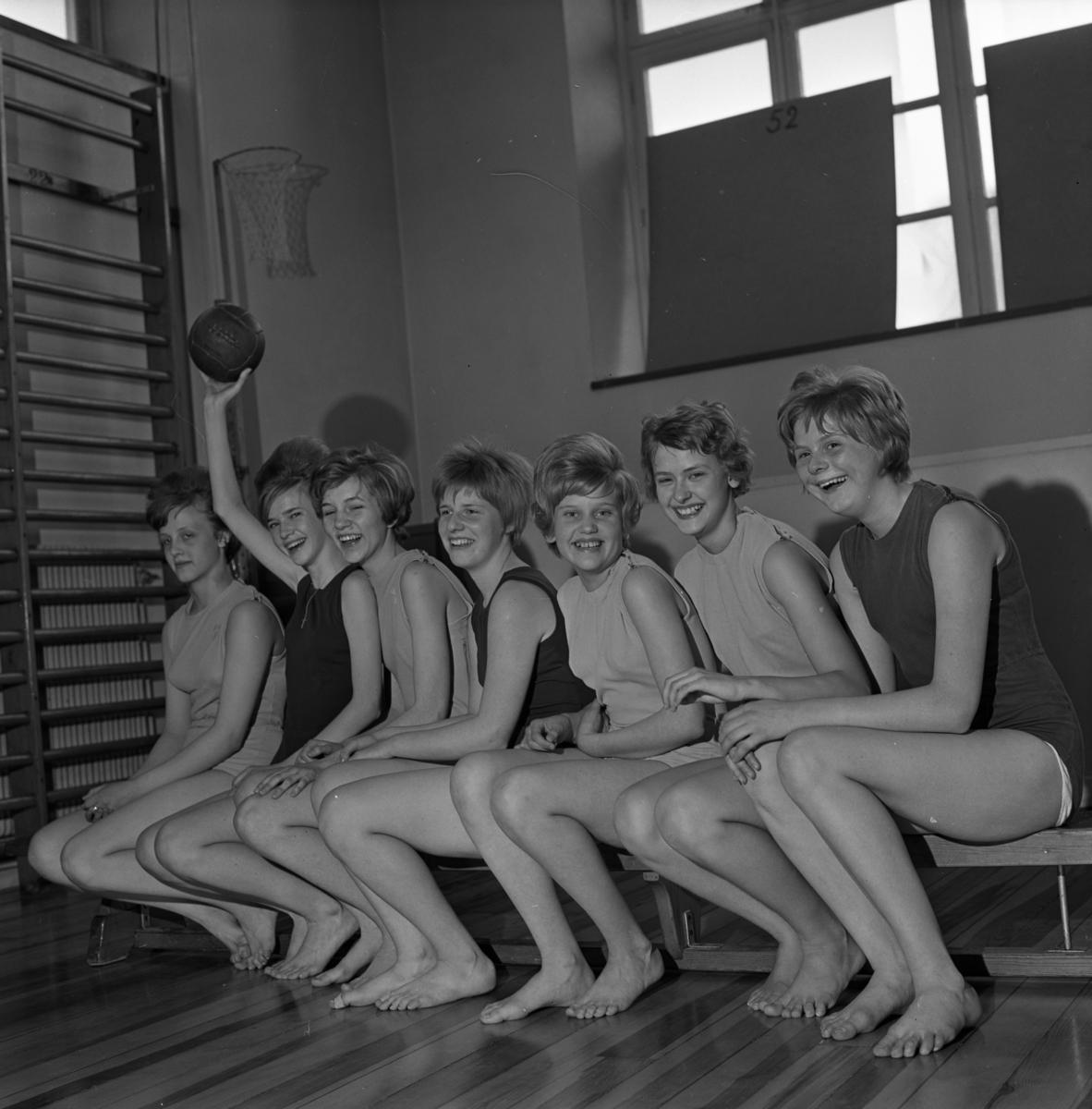 Skolturnering i korgboll/basket Sju flickor sitter på en gymnastikbänk. En ribbstol ses intill. Från vänster: Birgitta Karlsson, Ing-Marie Eriksson, Karin Knutsson, Kerstin Karlsson, Karin Hägg, Eva Olsson och Ann-Marie Eriksson