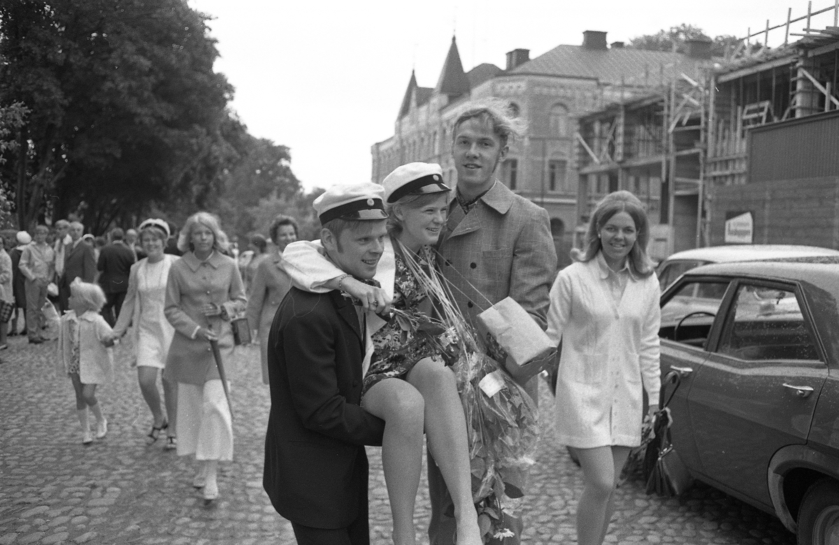 Studentdag! Kicki Holm, iklädd studentmössa och blombuketter, bärs av Anders Holm (i mössa) och Bo Pilerud. Det är mycket folk i rörelse på Järntorget.
