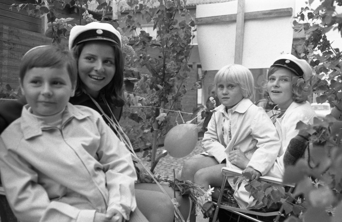 Studentdag! I lövat fordon färdas Susanne Levert (till vänster) och Kicki Holm (till höger). Två barn får åka med, oklart vilka de är.