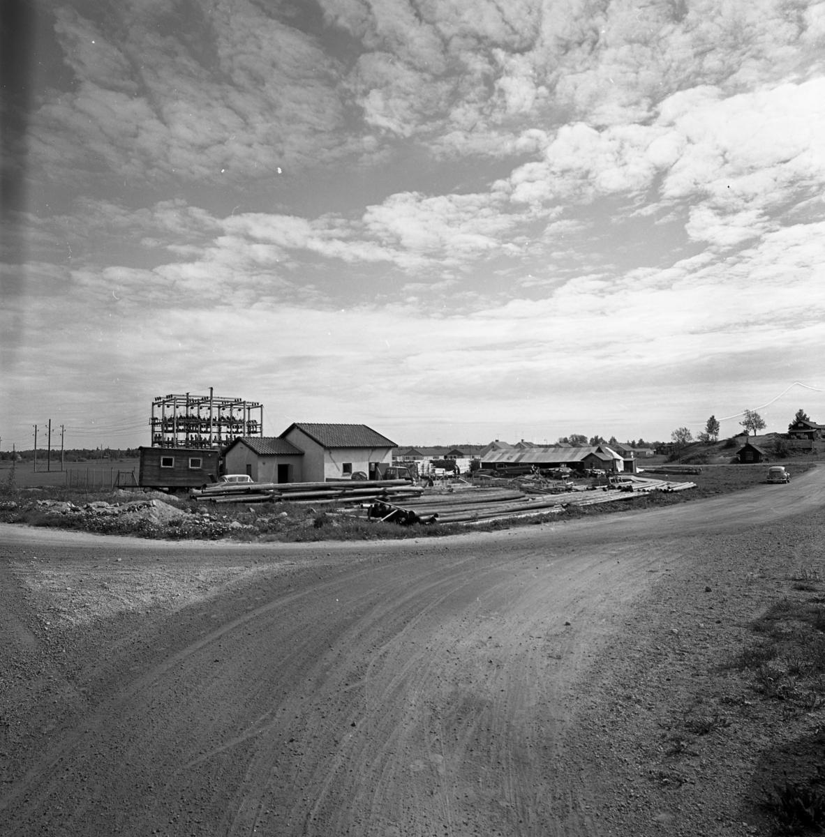 Sågen, sågverket, exteriör. Timmer ligger utanför. En grusväg i förgrunden. Husen, på kullen, ligger efter Prästgatan. Till vänster en transformatorstation.