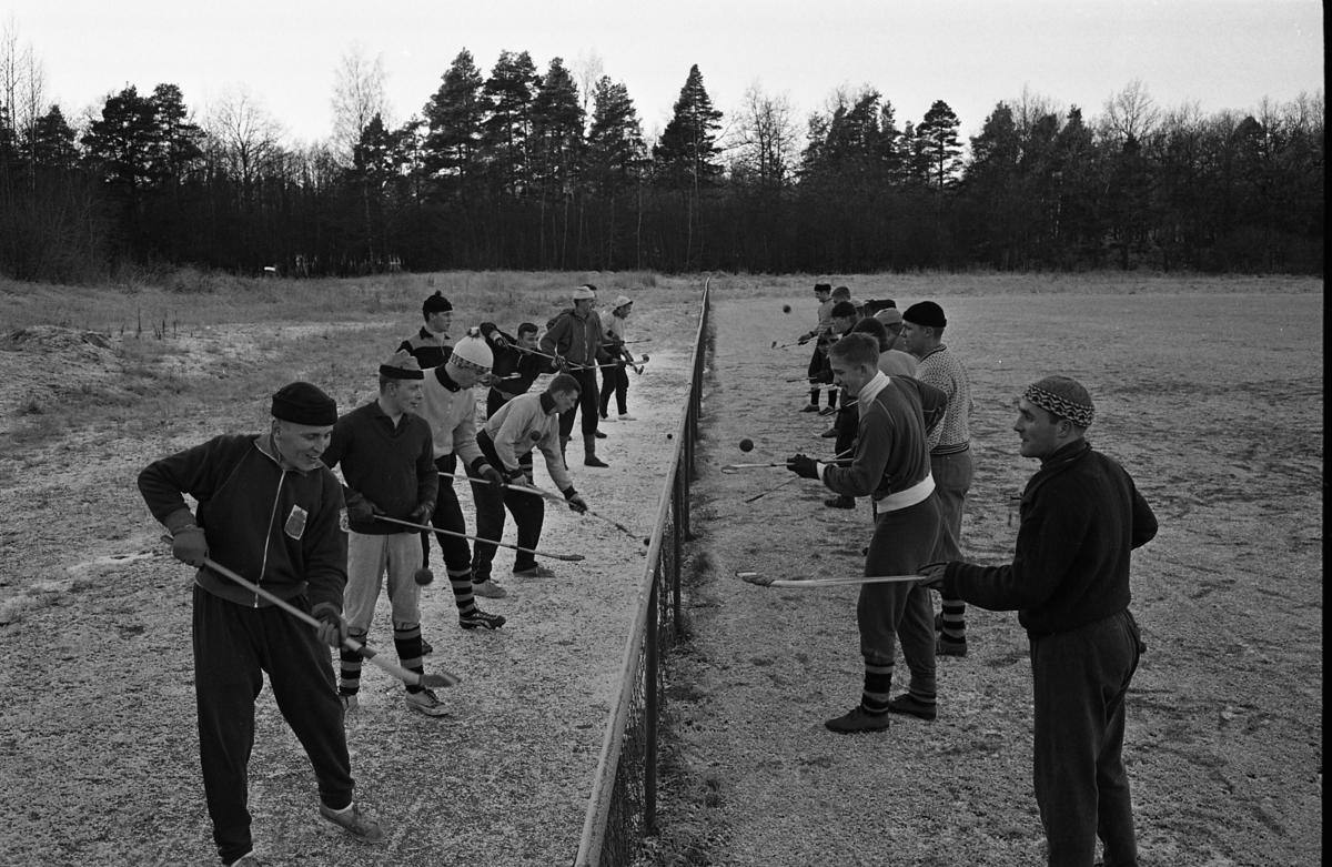 Södra IF har bandyträning. Nitton spelare står i två rader med ett nät mellan sig. De är utomhus. Arboga Södra