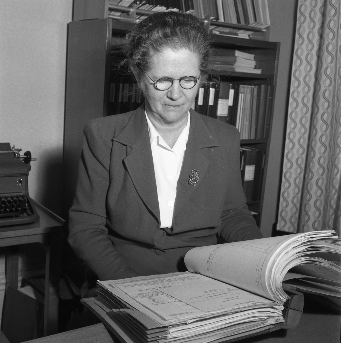 Telekommissarie Eva Geete på Televerket, Sohlénska huset, på Nygatan. Eva bär glasögon och är klädd i en dräktjacka med en brosch på slaget. Läs om Televerket och branden 1956 i Arboga Minnes årsbok 1993. Kvinna som sitter vid skrivbordet och bläddrar i en pärm. Bakom henne ses en skrivmaskin på ett lågt bord, en bokhylla med pärmar samt en gardin.