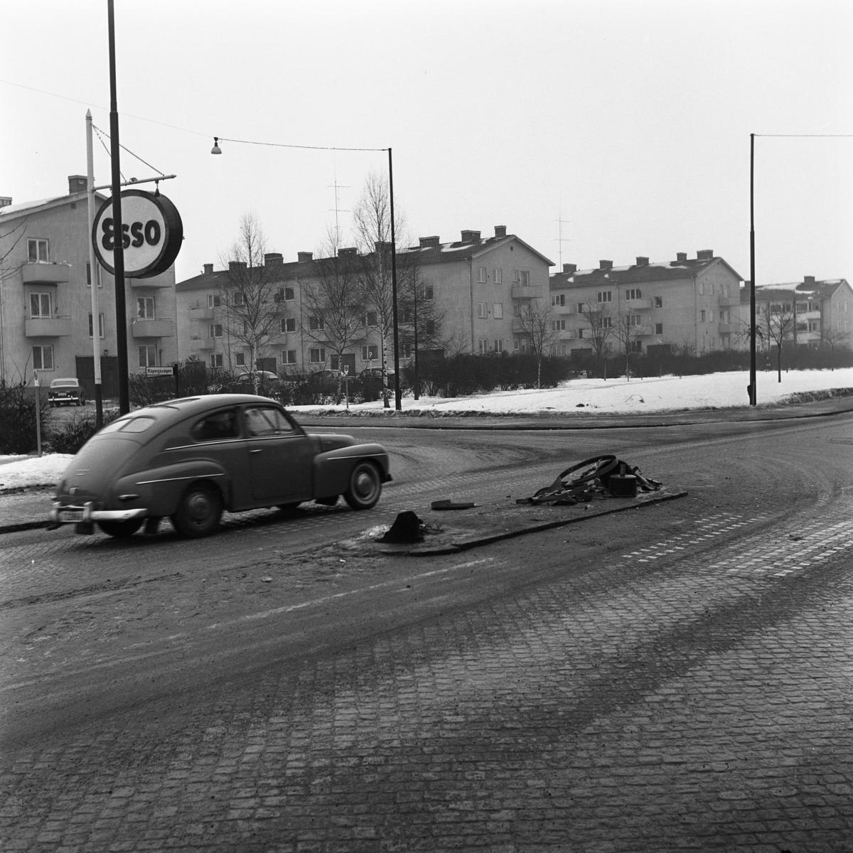 Trafikdelaren, vid järnvägsstationen, är sönderkörd av en lastbil.  I bilden ses en Volvo PV, en skylt till bensinmacken ESSO samt flerfamiljshus i Vasastan.