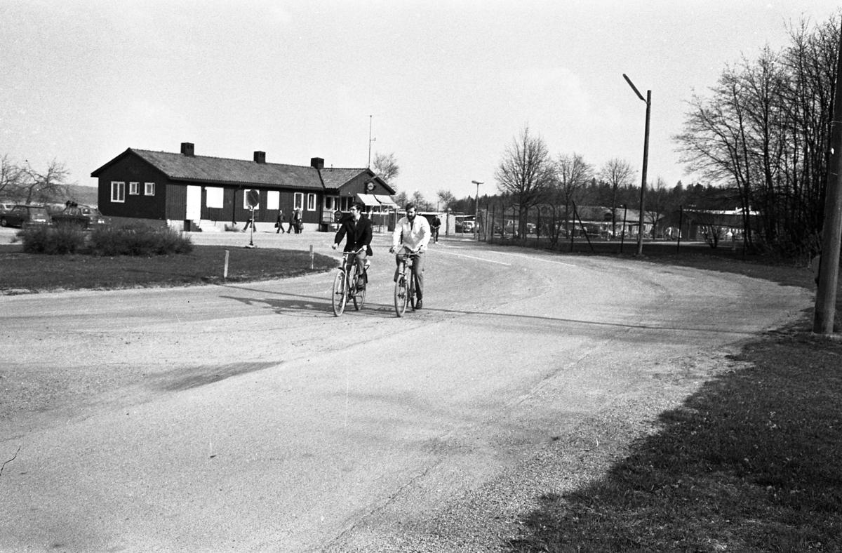 Två män cyklar hemåt efter ännu en arbetsdag på CVA, Centrala Verkstaden Arboga. I bakgrunden ses bilparkeringen, byggnaden där vakten sitter samt grinden där alla måste passera.