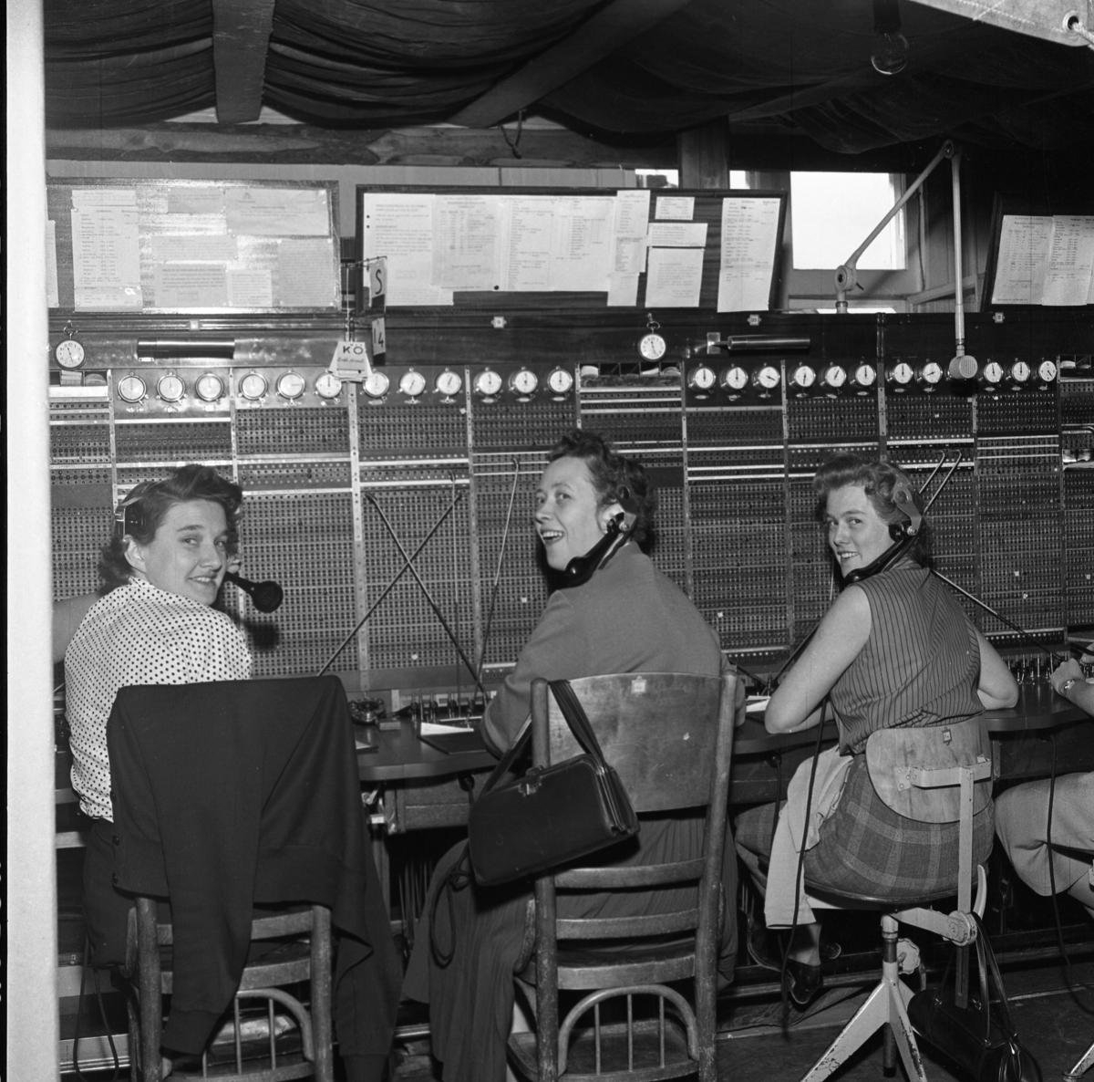 Telefonisterna fortsätter sitt arbete vid växelborden trots skadorna efter branden i fastigheten. En presenning är spänd över arbetsplatsen för att inte vatten, från släckningsarbetet, ska skada växeln. Klockorna, som hänger på rad, visar hur många perioder samtalen varat. Kvinnorna har en telefonlur hängande intill örat. Från vänster: okänd, Alice Ståhl och Britt Johansson. Televerket låg på Nygatan. Läs om Telefonen i Arboga och branden på Televerket 1956 i Arboga Minnes årsbok 1993.