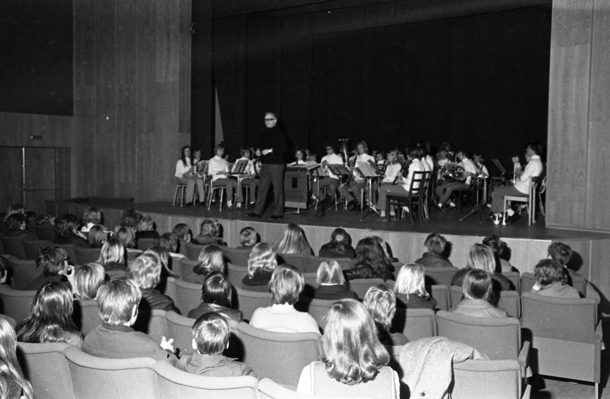 Ungdomsmusikkåren underhåller från scenen på Medborgarhuset. Dirigent är Karl-Axel Göransson. Publiken består av ungdomar som kanske är där på skoltid.