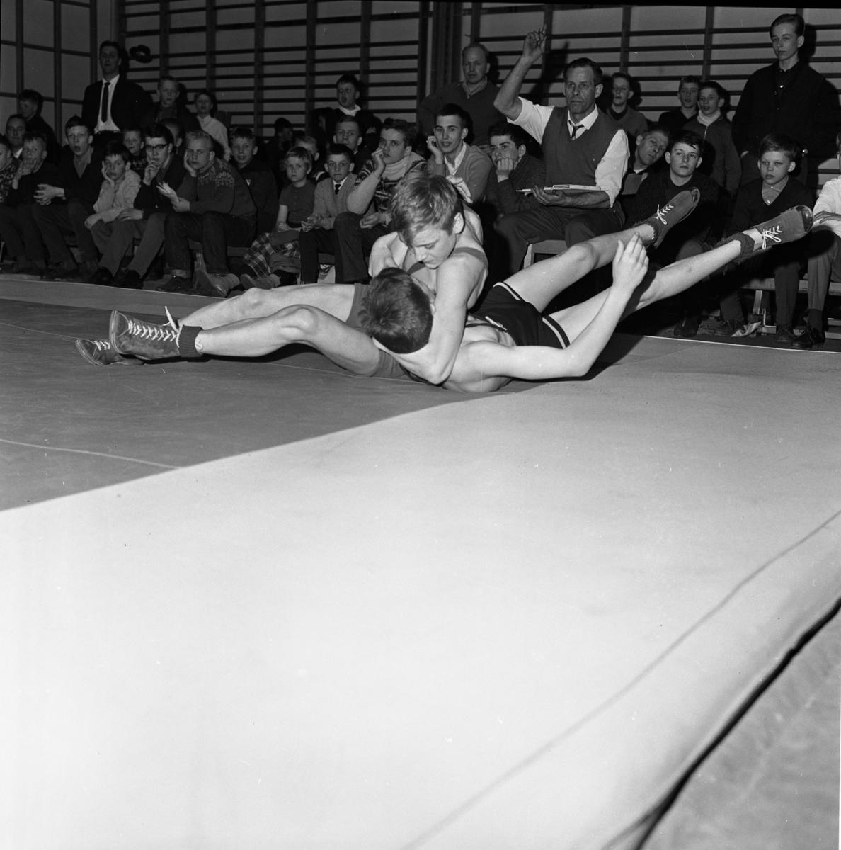 Ungdomsbrottning. Två brottare på mattan. Matchen äger rum i en gymnastiksal. Publiken sitter nedanför ribbstolarna.