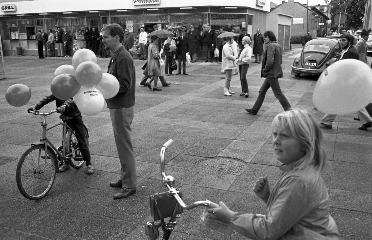 Valmöte på Nytorget. Grillen och Pressbyrån ses i bakgrunden. Folkvagnen svänger västerut, på Ahllöfsgatan. Mannen med ballongerna är Per-Olov Nilsson. Det är mycket folk i rörelse på torget. En del har paraply. I förgrunden ses några barn med cyklar.