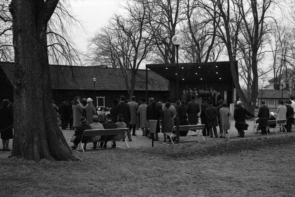 Valborgsmässoafton, sista april, firas i Olof Ahllöfs park. Publiken lyssnar till manskören som sjunger vårsånger från scenen. Kägelbanan ses till höger.