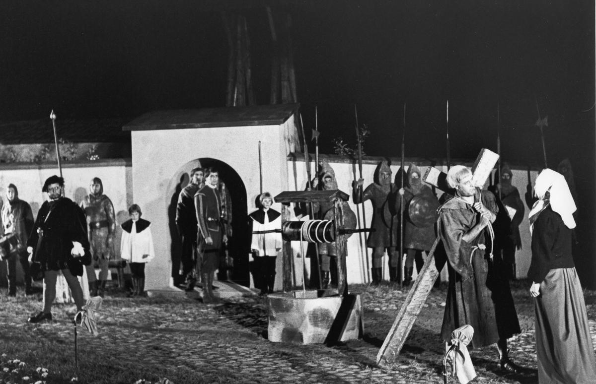 """En scen ur """"Giv oss fred"""". Engelbrekt Gertsson, till vänster, spelas av Rune Lindström. Vakter i rustningar står uppställda utanför en mur med portal. En man bär ett kors. Han talar med en kvinna. I när heten finns en brunn. """"Giv oss fred"""", även kallat """"Arbogaspelet"""", är ett teaterstycke skrivet av Rune Lindström 1961. Handlingen, som är inspirerad av Arbogas klosterhistoria, är förlagt till början av 1500-talet. Uruppförandet skedde den 11 augusti 1962 och Rune Lindström spelade Engelbrekt Gertsson. Lions Club i Arboga stod för arrangemanget. Föreställningarna regnade bort och det blev ett stort ekonomiskt bakslag för föreningen. Spelet har framförts igen; 1987, 1988, 2012 och 2015 av medlemmar i """"Bygdespelets Vänner""""."""
