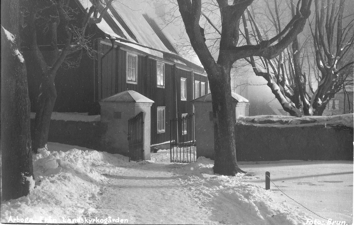 Snötäckt kyrkogård vid Landskyrkan/Sankt Nikolali kyrka Grindarna leder ut mot Östra Nygatan. Fotografiet har vykortsbaksida