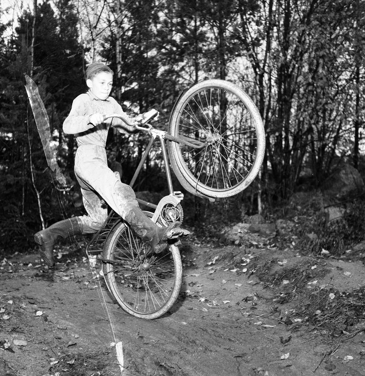 """Cykelcross är en ny sportfluga för ungdomar. Här kommer Nils Karlsson, tävlande för Arbogas Kronorna. Laget möter Rövarna från Fellingsbro som tävlar på hemmaplan. Banan är 450 meter lång. Den här bilden finns med i Reinhold Carlssons bok """"Arboga objektivt sett""""."""