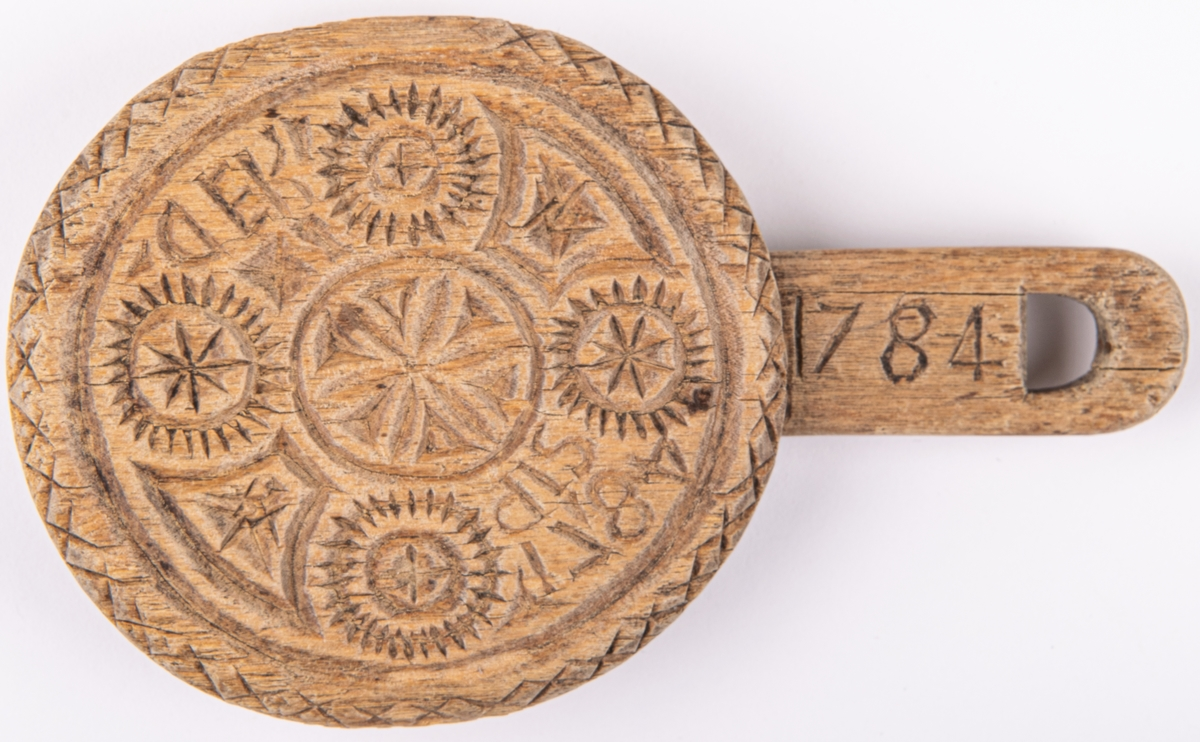 Acc.kat. Smörstämpel märkt 1784 PIS KED.  Lappkort. Smörstämpel av trä, rund med kort skaft i sidan. Utskurna reliefer; rosor mm. På skaftet ristat: PIS KED 1784.